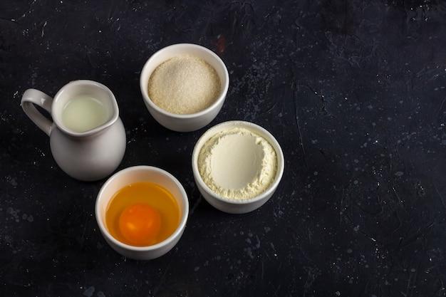 Выпечка фон. ингредиенты для приготовления торта (мука, яйцо, сахар, молоко) в мисках на темном столе. концепция питания. закройте макет, скопируйте пространство для текста