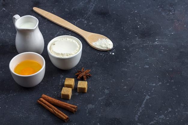 Выпечка фон. ингредиенты для приготовления торта (мука, яйцо, молоко, анис, корица, тростниковый сахар) в мисках на темном столе. концепция питания. закройте макет, скопируйте пространство для текста