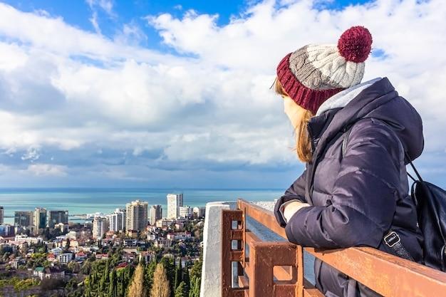 Взгляд со стороны молодой женщины смотря в расстояние на ландшафте моря. вид со смотровой площадки (смотровая площадка). туристическая прогулка, экскурсии и экскурсии концептуальный текст.