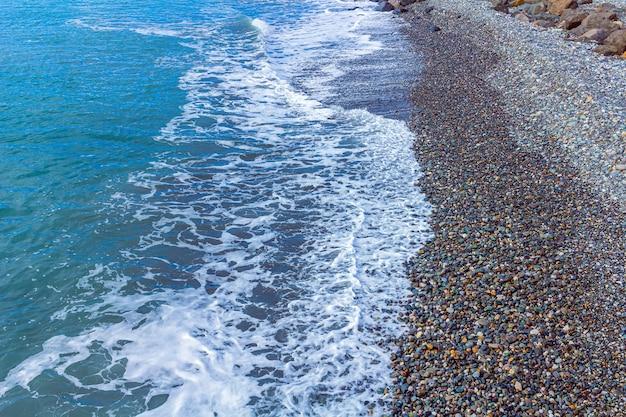 曇り空を背景にビーチで小石と曇りの悪天候で海の風景。小さな波と寒い冬の海。