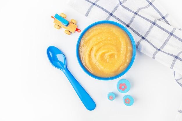 Детская еда. свежее домашнее яблочное пюре. синий шар с фруктовым пюре на ткани и детские игрушки на столе. концепция правильного питания и здорового питания. органическая и вегетарианская еда. скопируйте место для текста