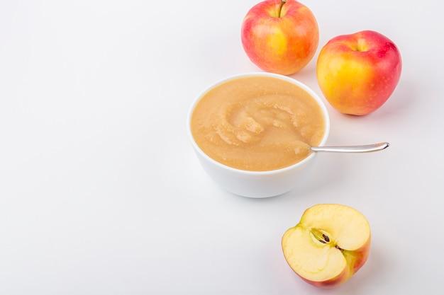 Свежее домашнее яблочное пюре. концепция правильного питания и здорового питания. органическая и вегетарианская еда. белый шар с фруктовым пюре на ткани и нарезанные яблоки на столе. детская еда. копировать пространство