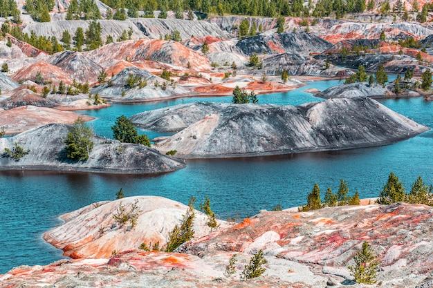 Апокалиптический пейзаж, похожий на поверхность планеты марс. фантастический вид на голубое озеро. затвердевшая красно-коричневая черноземная поверхность. бесплодная, потрескавшаяся и выжженная земля. концепция глобального потепления.