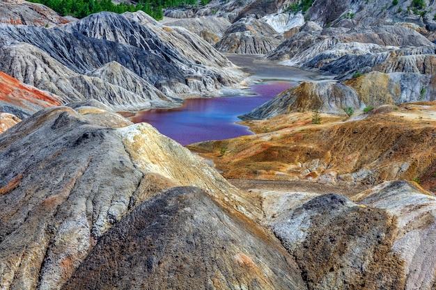 Апокалиптический пейзаж, похожий на поверхность планеты марс. фантастический вид на малиново-красное озеро. затвердевшая красно-коричневая черноземная поверхность. бесплодная, потрескавшаяся и выжженная земля. концепция глобального потепления