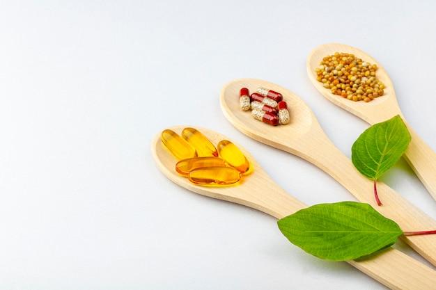 ハーブカプセル、天然ビタミン、白い背景の上の木のスプーンでミネラルのサプリメント。ヘルスケアと代替医療の概念:ホメオパシーと自然療法。フラット横たわっていた、テキストのコピースペース