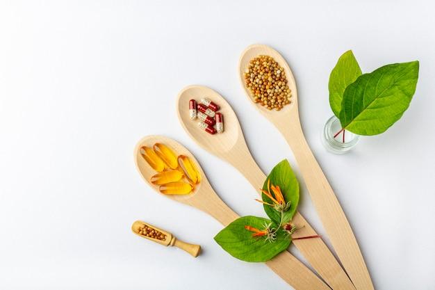 ハーブカプセル、天然ビタミン、白い背景の上の木のスプーンで乾燥キンセンカの花。ヘルスケアと代替医療の概念:ホメオパシーと自然療法。フラットレイアウト、コピースペース