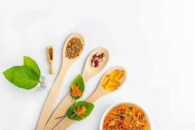 Травяная капсула, натуральные витамины, сухие цветки календулы на деревянной ложкой на белой поверхности. концепция здравоохранения и нетрадиционной медицины: гомеопатия и натуропатия.