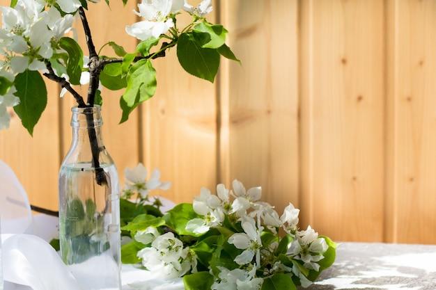 Винтажное стекло, мини стеклянная бутылка с цветущими ветвями вишни, груши, яблока на деревянной стене. цветочная композиция в теплый весенний солнечный день.