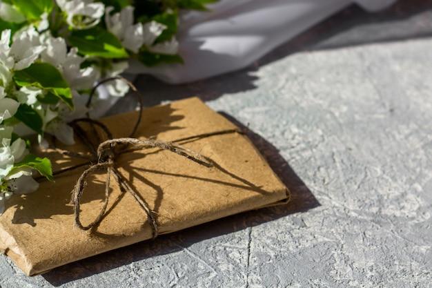 Цветущие ветви вишни, яблони на сером фоне. цветочная композиция. милая подарочная коробка обернутая с коричневой крафт-бумагой и украшенная джутом, взгляд сверху, с космосом для текста.