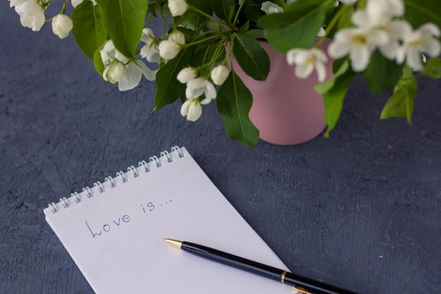 Цветочная композиция в весенний день. цветущие ветви яблони в розовой мини вазе на сером фоне. блокнот с пространством для текста. концепция написания романтического письма.
