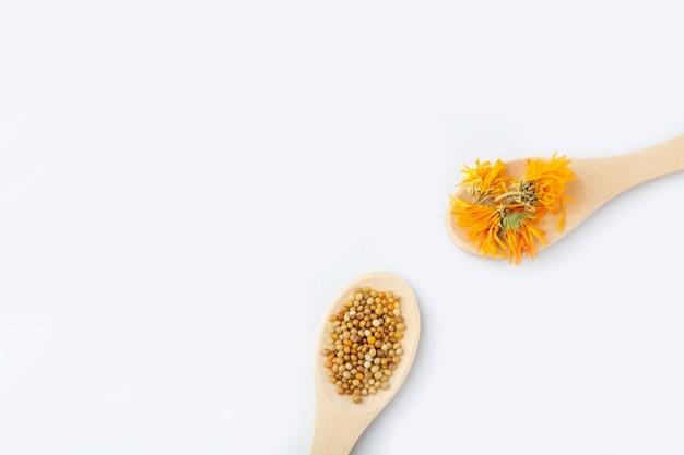 ハーブカプセル、天然ビタミン、白い背景の上の木のスプーンで乾燥キンセンカの花。ヘルスケアと代替医療の概念:ホメオパシーと自然療法。クローズアップ、テキストのスペースをコピー