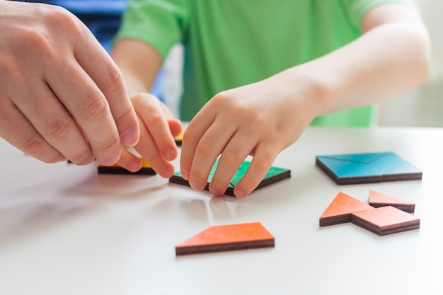 Пребывание дома, социальное расстояние и самоизоляция во время концепции карантина семейный досуг. отец и сын играют в логические игры и деревянные головоломки. выборочный фокус. детские развивающие игры