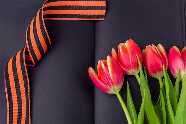 Шаблон пустой поздравительной открытки. красные цветы (тюльпаны), георгиевская ленточка на черной тетради. день победы или день защитника отечества концепции. вид сверху, скопируйте пространство для текста
