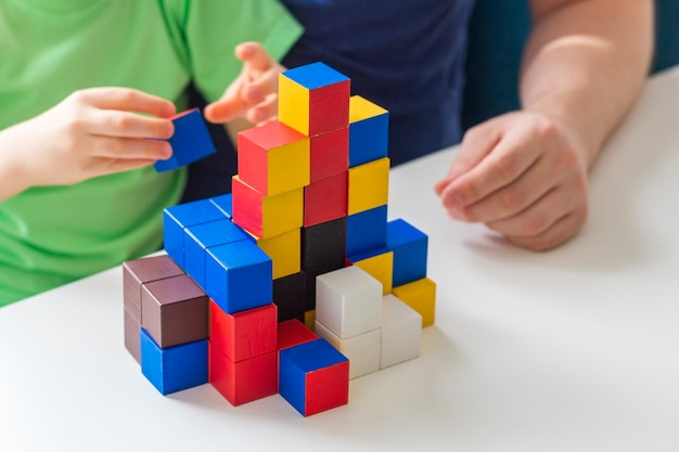 隔離の概念の間に家にいて、社会的距離と自己隔離をしてください。家族でのレジャー。父と息子が論理ゲームと木製パズルをします。セレクティブフォーカス。子供の教育ゲーム