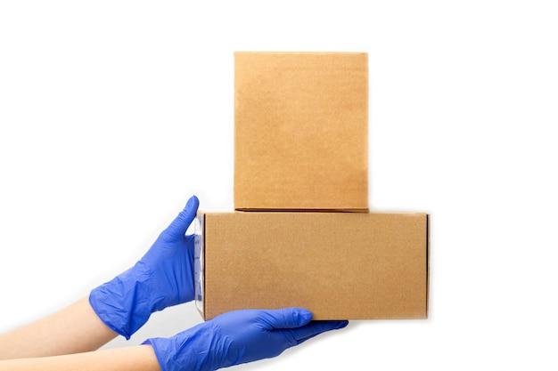 Служба доставки во время карантина. рука в резиновых перчатках держит картонную коробку. оставайтесь дома, делайте покупки в интернете во время вспышки коронавируса.