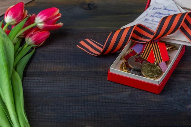 День победы фон. георгиевская ленточка, фронтовые письма, военная гарнизонная шапка и ордена на деревянном фоне.