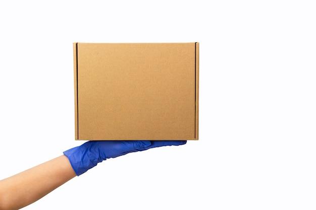 Служба доставки во время карантина. рука молодой женщины в резиновых перчатках держит картонную коробку изолированный на белизне. оставайтесь дома, делайте покупки в интернете во время вспышки коронавируса.