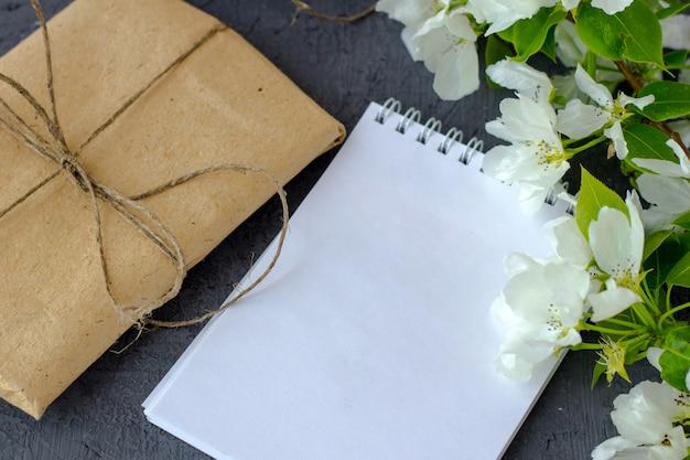 灰色の背景にリンゴの木の開花枝。テキスト用のスペースを持つノートブック。茶色のクラフトペーパーで包まれ、バレンタインデーのためにジュートで飾られたかわいいギフトボックス