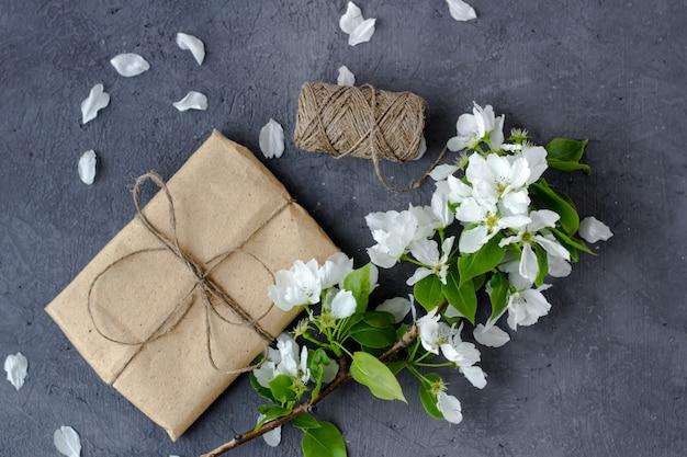 灰色の背景に桜、リンゴの木の開花枝。花の組成物。茶色のクラフトペーパーで包まれ、ジュート、平面図、テキスト用のスペースで飾られたかわいいギフトボックス