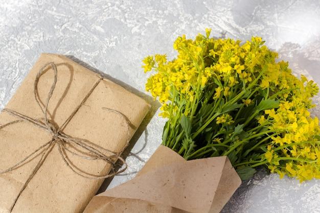 灰色の背景、上面にクラフトペーパーで野生の花の花束。新鮮な春の花。クラフト紙で包んだギフトボックス。