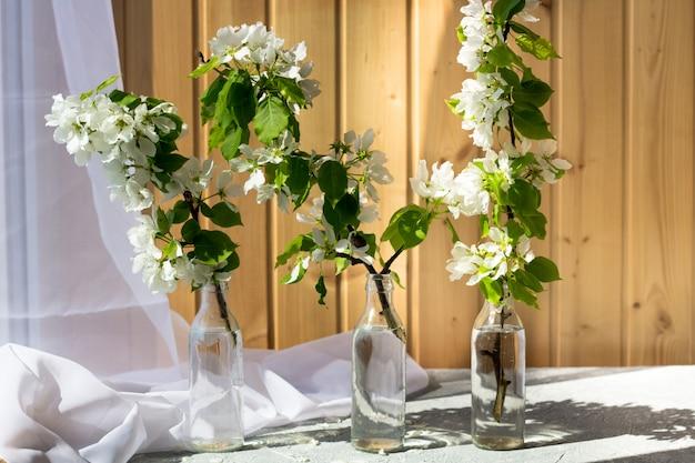 Винтажное стекло, мини стеклянная бутылка с цветущими ветвями вишни, груши, яблока на деревянном