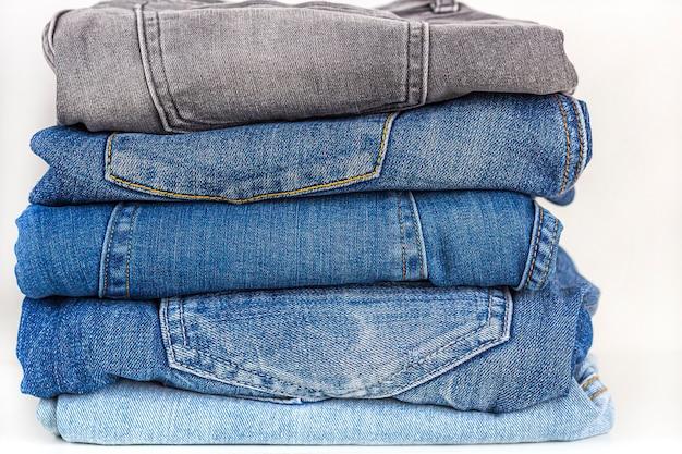 Аккуратный стек различных оттенков синих джинсов на белой полке. хранение одежды. прачечная и выглаженная джинсовая одежда.