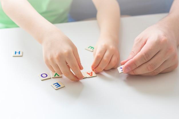 隔離の概念の間に家にいて、社会的距離と自己隔離をしてください。家族でのレジャー。父と息子が論理ゲームと木製パズルをします。
