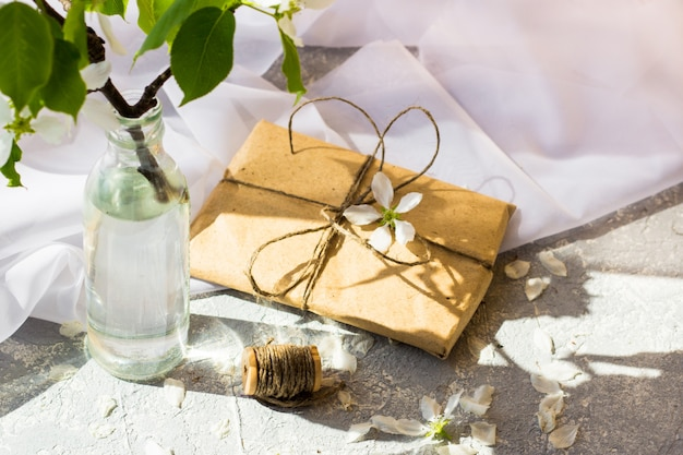 Стеклянная бутылка с цветущими ветвями вишни, яблони на деревянном фоне. цветочная композиция на весенний солнечный день.