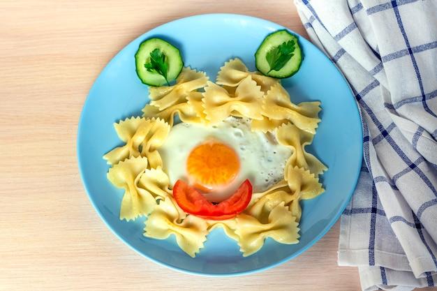 子供の食べ物。面白い食べ物。変な顔の形で目玉焼きと野菜のパスタプレート。お子様メニューとランチのコンセプトです。