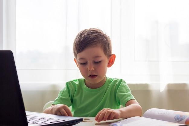 遠隔学習、オンライン教育。隔離期間中の社会的距離と自己隔離。ノートブックで自宅で勉強し、開発学校の宿題をする幼児または少年。