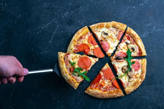 女性の手は、料理用シャベルでピザを保持しています。暗い背景にサラミとチーズの作りたてのペパロニピザ。イタリアの伝統的なランチまたはディナー。ファーストフードとストリートフードのコンセプトです。
