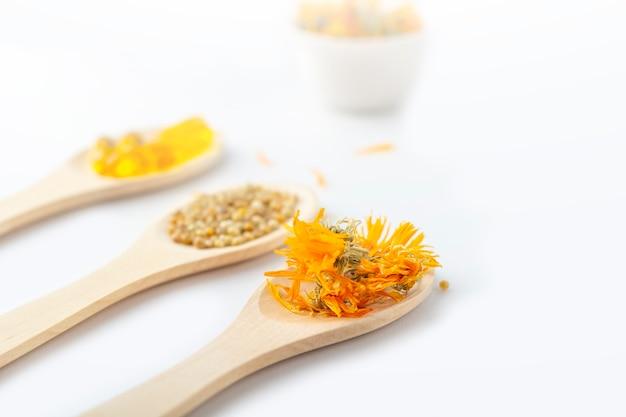 ハーブカプセル、天然ビタミン、白い背景の上の木のスプーンで乾燥キンセンカの花。ヘルスケアと代替医療の概念:ホメオパシーと自然療法。