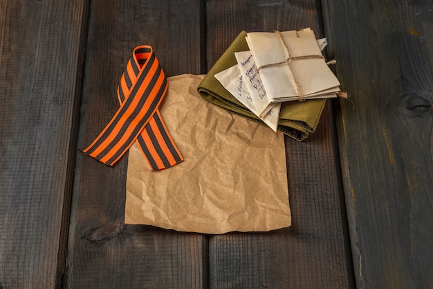 День победы фон. георгиевская ленточка, передовые буквы, военная гарнизонная фуражка на деревянном фоне.