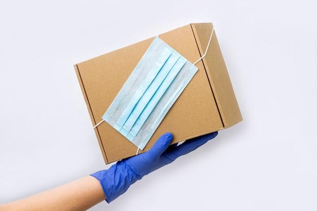 Служба доставки во время карантина. рука молодой женщины в резиновых перчатках держит картонную коробку с защитной медицинской маской. оставайтесь дома, делайте покупки в интернете во время вспышки коронавируса.