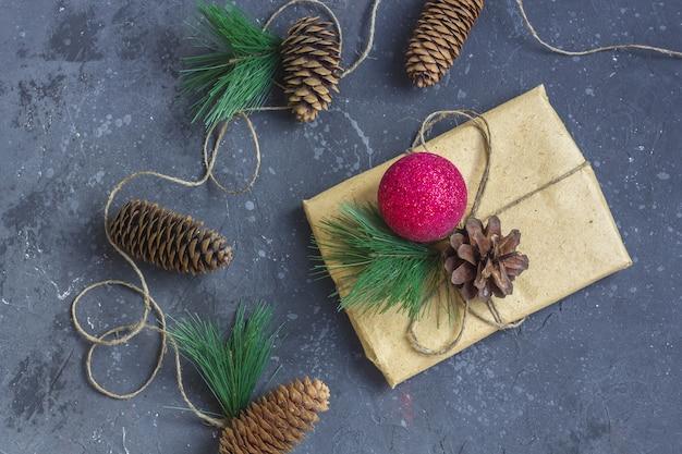 クリスマスの組成物。クラフト紙、モミの木の枝、松ぼっくり、赤い装飾でギフト包装