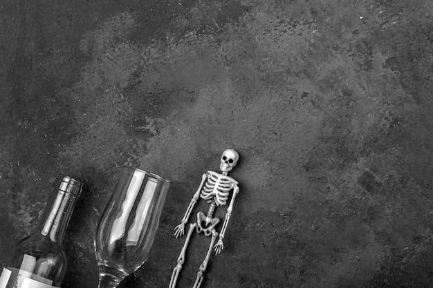 アルコール消費による人格破壊の概念。人間の骨格、ワイングラス、ボトル。アルコール中毒と飲酒。