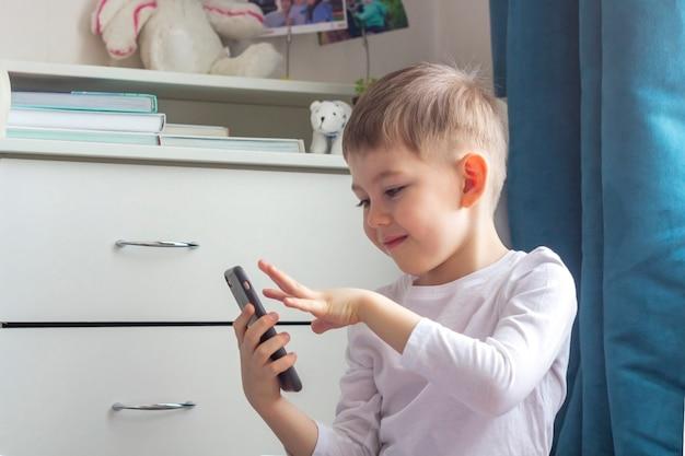 幸せな子供は彼のお父さん、お母さん、おじいちゃん、おばあちゃんにスマートフォンでビデオ通話をします。隔離の概念の間に家にいて、社会的距離と自己隔離をしてください。