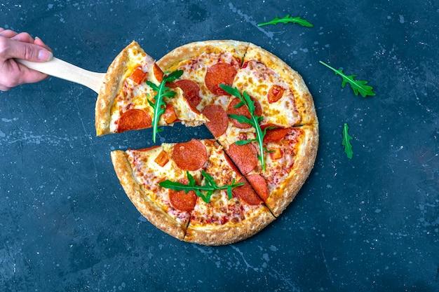 女性の手は、料理用シャベルでピザを保持しています。暗い背景にサラミとチーズの作りたてのペパロニピザ。イタリアの伝統的なランチまたはディナー。