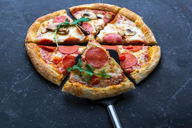 暗い背景にサラミ、マッシュルーム、ハム、チーズの作りたてのピザ。イタリアの伝統的なランチまたはディナー。