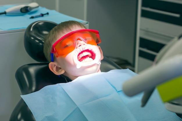Детская стоматология. детское стоматологическое обследование молочных зубов. эмоции ребенка в стоматологическом кресле. маленький мальчик в защитных оранжевых очках