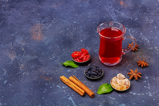 Красный чай в турецкой чайной чашке с кизилом, изюмом, сахаром в восточном стиле на темном