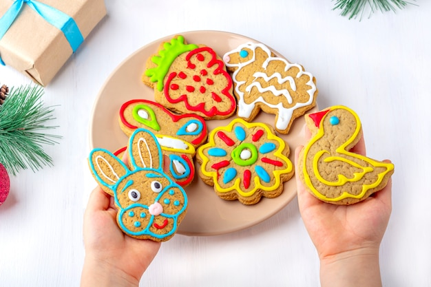 子供は、モミの枝やプレゼントの中で白い木製の背景にジンジャーブレッド(クッキー)を保持しています。クリスマスと新年の甘いギフトコンセプト。