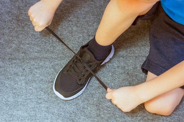 Ребенок надел кроссовки. ноги молодого мальчика в текстильной моды черные кроссовки. детская модная повседневная одежда и уличная мода. закрыть