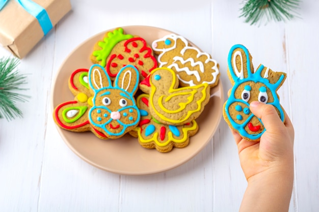 子供は、モミの枝とコーンの中で白い木製の背景にジンジャーブレッド(クッキー)を保持しています。クリスマスと新年の甘いギフトコンセプト。