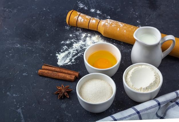 Выпечка фон. ингредиенты и посуда для приготовления торта на темном столе. концепция питания. закройте, скопируйте пространство для текста.