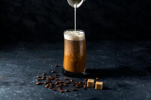 Ледяной кофе фраппе в высокий стакан. прохладный летний напиток на темном фоне в низком ключе. поток молока льется в кофе.