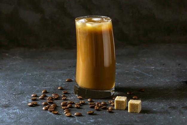 Ледяной кофе фраппе в высокий стакан. прохладный летний напиток на темном фоне в низком ключе.