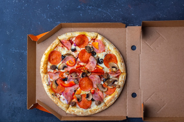 持ち帰り配達サービス。暗い背景にキノコ、ハム、チーズと作りたてのピザの段ボール箱を開けた。ファーストフードのコンセプト。