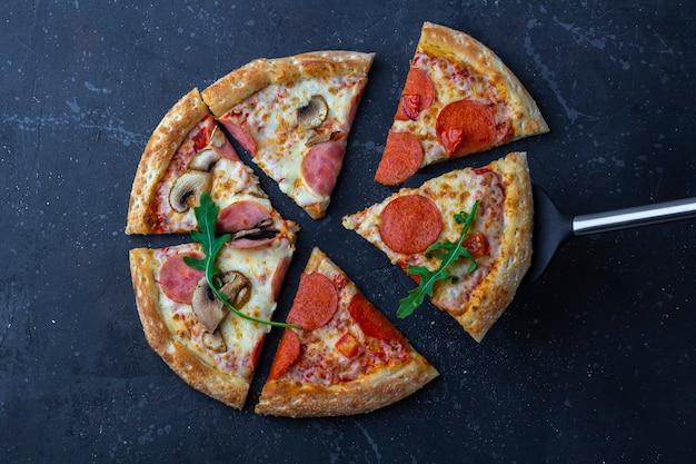 暗い背景にサラミ、マッシュルーム、ハム、チーズの作りたてのピザ。イタリアの伝統的なランチまたはディナー。ファーストフードとストリートフードのコンセプト。