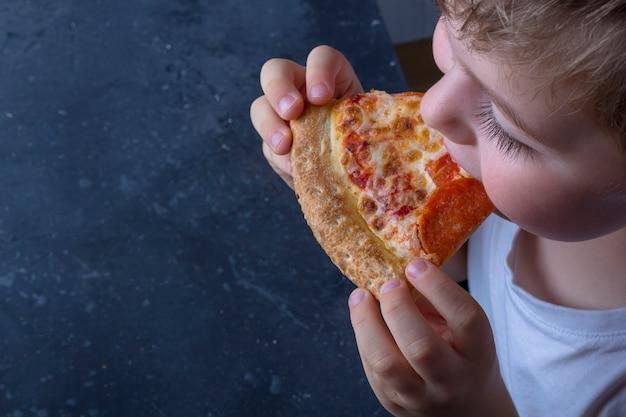 Голодный ребенок ест пиццу пепперони аппетит в домашних условиях. закройте итальянский традиционный обед или ужин. детская закуска